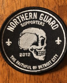 "A black, circle shaped patch, three inches in diameter. Along the top are the words ""Northern Guard Supporters"" and the ""The Faithful of Detroit City"" along the bottom. The Northern Guard skull, in profile, is in the middle."