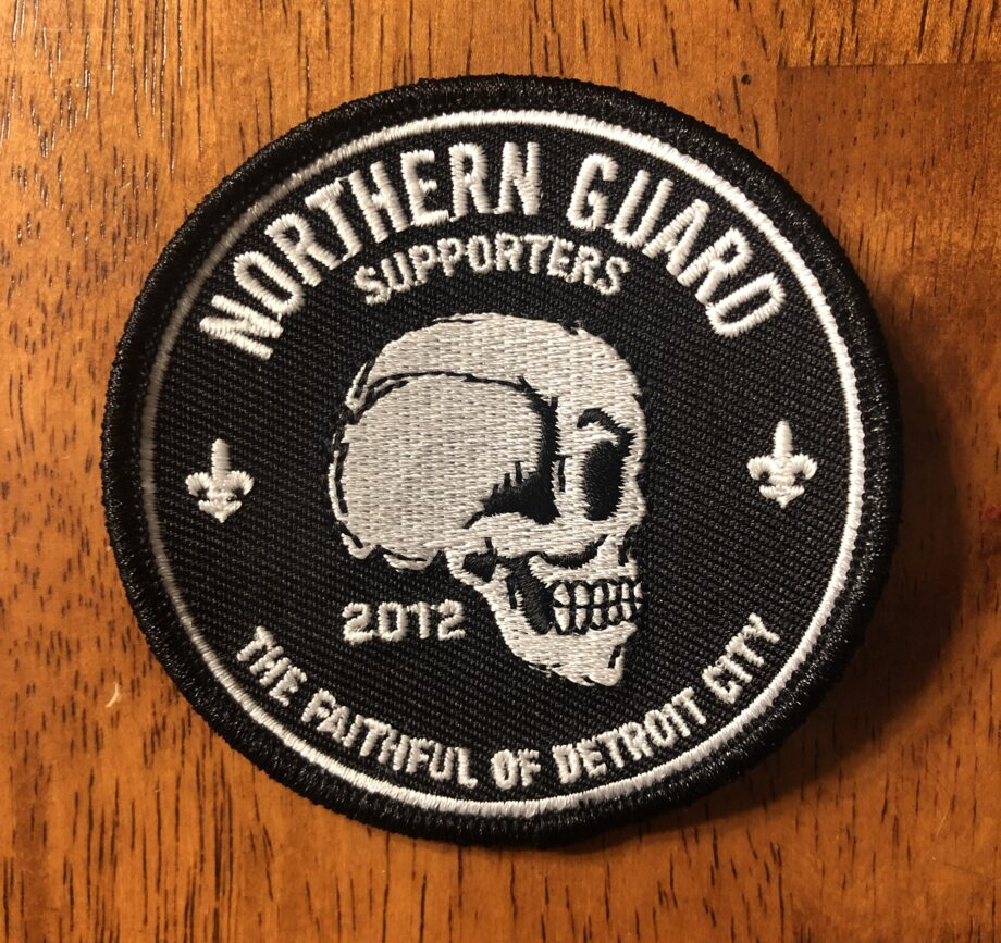 """A black, circle shaped patch, three inches in diameter. Along the top are the words """"Northern Guard Supporters"""" and the """"The Faithful of Detroit City"""" along the bottom. The Northern Guard skull, in profile, is in the middle."""